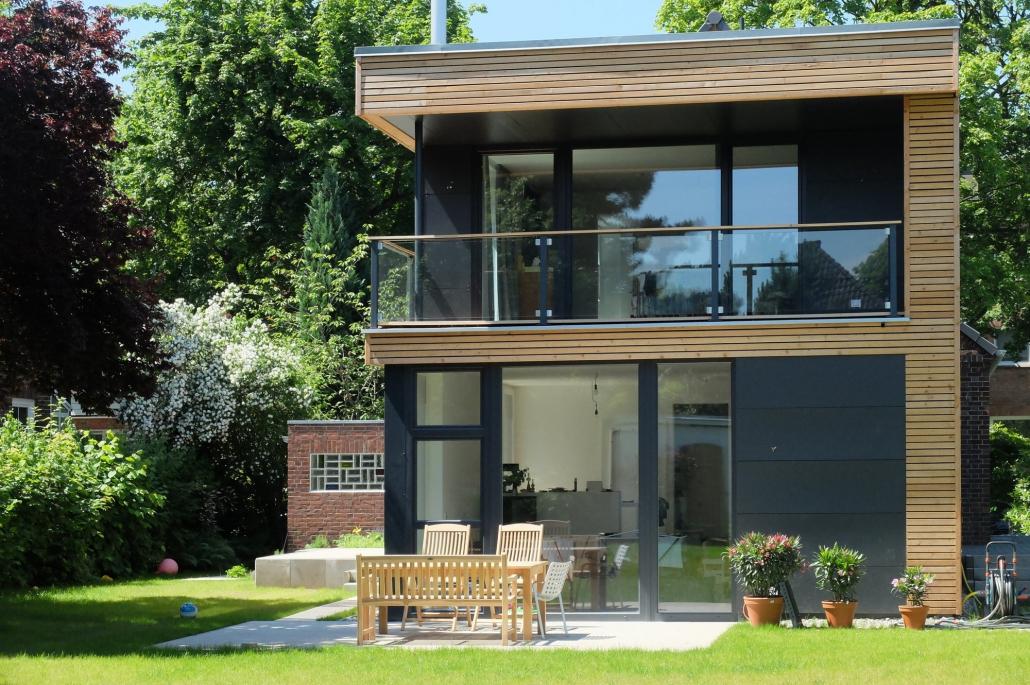 Modernes, dunkles Haus mit zwei Etagen, Terasse sowie großen Fenstern