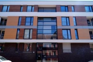 Außenansicht des Gebäudes mit hellem und dunklem Holz verziert