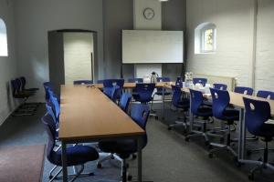 Ein Besprechungsraum mit Tischen und blauen Stühlen sowie einem Whiteboard, auf dem einige Notizen stehen