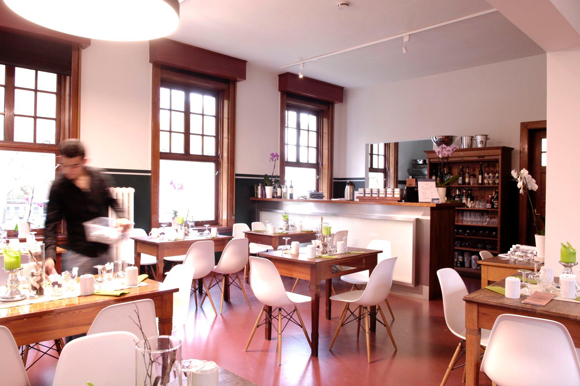 Das Restaurant mit vielen Stühlen und einem Kellner in Aktion