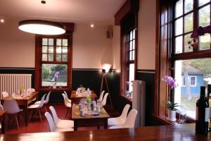 Das Restaurant in kompletter Ansicht mit dunklen Tischen, weißen Stühlen und grün-weißer Tischdekoration