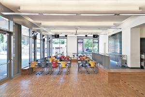 Eine leere Cafeteria mit bunten Stühlen, vom Eingang aus fotografiert