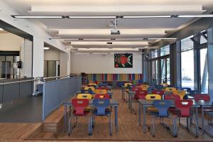 Eine leere Cafeteria mit bunten Stühlen, von den Fenstern aus fotografiert