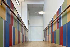 Ein langer Flur mit bunt gekachelten Wänden