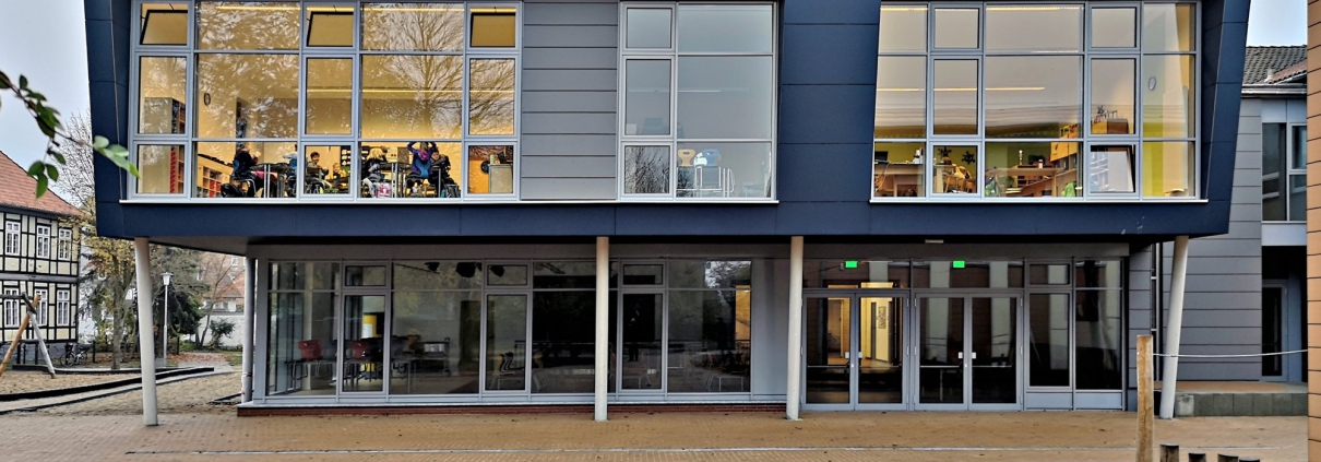Die Fassade des blauen Schulgebäudes mit Einblick in einige Klassenräume