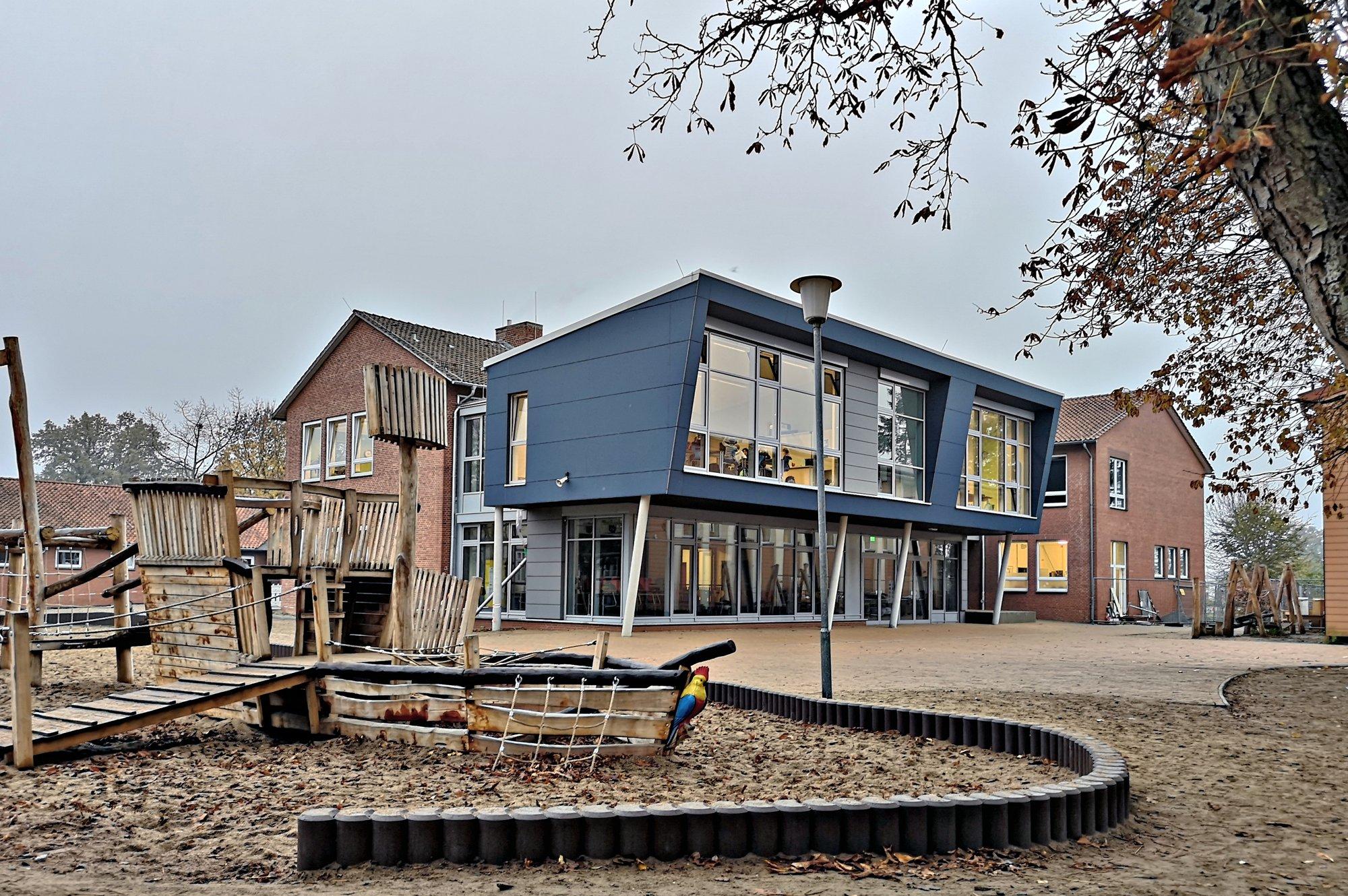 Ein Spielplatz vor dem blauen Schulgebäude der Elbtalschule in Bleckede