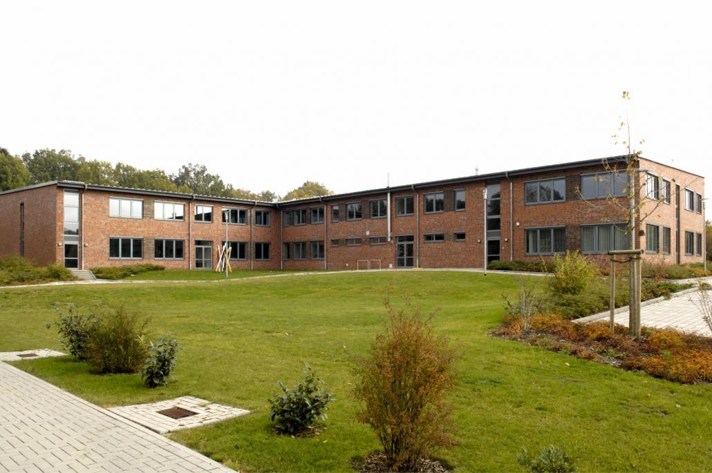 Eine große Grünfläche mit einem flachen, rot-braunen Schulgebäude