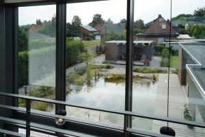 Ausblick aus der oberen Etage auf die Terasse und den kleinen Teich