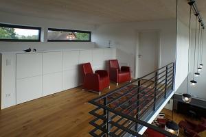 Obere Etage mit zwei roten Sesseln und Geländer, vor dem man in die untere Etage schauen kann