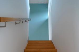 Treppenaufgang, der vor einer hellblauen Wand endet