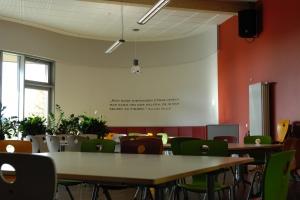 Viele Stühle und Tische in einem Aufenthaltsraum mit hoher Decke der Schule