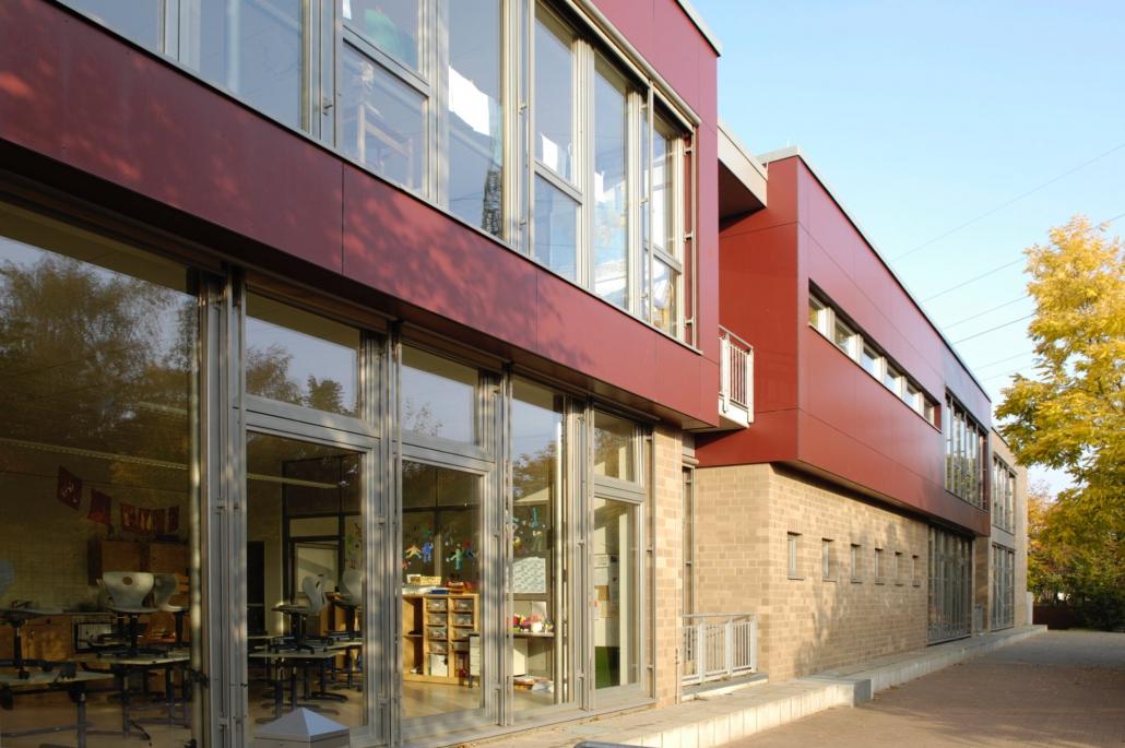 Ein rotes Schulgebäude, schräg fotografiert, mit großen Fenstern