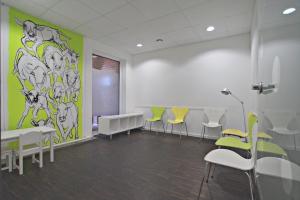 Ein großes Wartezimmer mit grünen, gelben und weißen Stühlen und einer abstrakt bezeichneten Wand